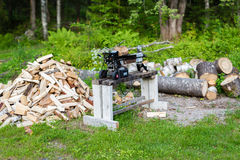 Firewood in a pile beside a woodcutter. Firewood in a pile beside a little woodcutter Royalty Free Stock Photo