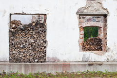 Firewood piles in window hole. Firewood pile in window hole of old building Royalty Free Stock Images