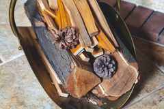 Firewood and pine cones lie in drow basket Stock Images