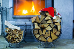 Firewood with Santa Claus hat in the house near a Royalty Free Stock Photos