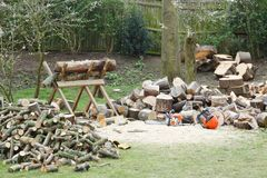Firewood and chainsaw in a garden. Firewood on a saw horse with chainsaw next to piles of firewood in a garden setting royalty free stock photos