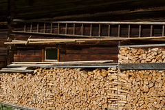 Firewood stacked by the alpine hut. Rural farming scene Royalty Free Stock Photography