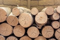 Firewood stacked in a decorative fireplace against the backdrop of artificial stone bricks stock image