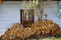 Firewood stacked near the old wooden cabin Stock Image