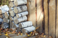 Firewood stacked near the wooden fence Royalty Free Stock Image
