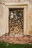 Firewood stacked in the opening of the window. Firewood stacked in the opening window with peeling plaster Stock Photography
