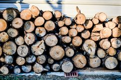 Firewood stacked up in front of a metal buidling. Firewood stacked up on some slab boards. Small logs, big logs. in-front of a metal building. Colors of the logs Stock Photo