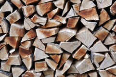Firewood stacked in wood shed Stock Photos