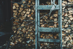 Firewood stock with old wooden ladder Royalty Free Stock Photo