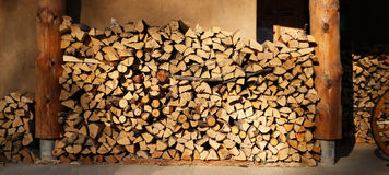 Firewood stored in front of a traditional wooden plastered house. Texture of firewood in front of a traditional wooden house Stock Image