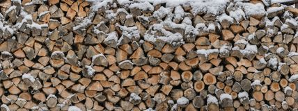 Firewood is stored in the snow as a wooden texture royalty free stock images