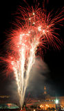 Firework. Celebratory fireworks in the night sky above the roofs Stock Image