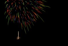 Colorful firework explosion in dark night sky with firing rocket royalty free stock images