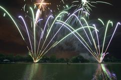 Firework display over lake. Exploding fireworks over lake at night Royalty Free Stock Photos