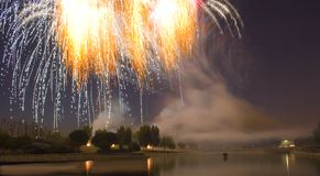 Firework display over lake. Exploding fireworks over lake at night Stock Image