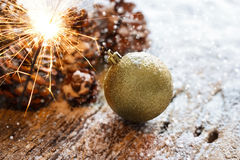 Firework or electric sparklers on christmas ornament pine cones Stock Photos