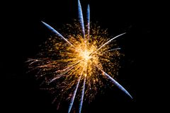 Firework Feather Starburst. A bright and brilliant time lapse photo of one large firework blast with a blue feathered starburst on a natural black sky background stock photo