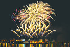 Firework over city at night with reflection in water Royalty Free Stock Image
