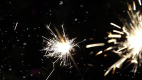 Firework sparkler burning with dancing snowflakes against black night sky background. Winter time blizzard. stock video footage