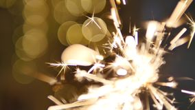 Firework sparkler burning with lights in background Royalty Free Stock Photography