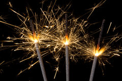 Firework sparklers. Three burning gold firework sparklers emitting sparks against a black background Stock Photography