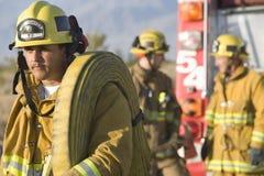 Fireworker som bär Firehose på hans skuldra royaltyfri fotografi