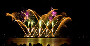 Fireworks. Pyrotechnic display shot from a barge with nice water reflection of the fireworks and silhouettes royalty free stock photo