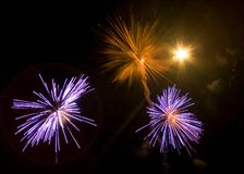 Fireworks. A view of several simultaneous purple and orange fireworks explosions in the night sky Stock Image