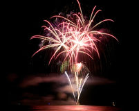 Fireworks. Colorful Fireworks over water at night royalty free stock photo