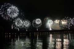 Fireworks. Long line of white or silver fireworks with reflections in a lake Royalty Free Stock Image