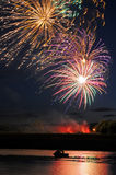 Fireworks Above Boat and River Stock Image