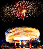 Fireworks at the Amusement Park. Fireworks exploding over a ride at the amusement park Stock Image