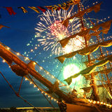 Fireworks behind a ship. Fireworks on water behind a ship seen between the mast and the sails Royalty Free Stock Photography