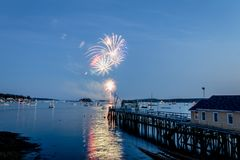 Fireworks on Boothbay Harbor, Maine, reflect off the water on July 4th. For Independence Day celebration stock photo