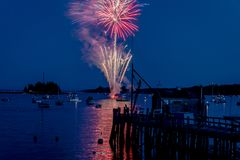 Fireworks on Boothbay Harbor, Maine, reflect off the water on July 4th. For Independence Day celebration stock images