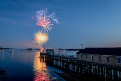 Fireworks on Boothbay Harbor, Maine, reflect off the water on July 4th. For Independence Day celebration royalty free stock images