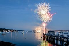 Fireworks on Boothbay Harbor, Maine, reflect off the water on July 4th. For Independence Day celebration royalty free stock photography