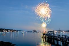 Fireworks on Boothbay Harbor, Maine, reflect off the water on July 4th. For Independence Day celebration royalty free stock photo