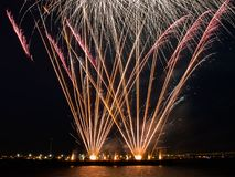 Fireworks burst in the night sky with light trails and clear base of fireworks over the sea Stock Photography