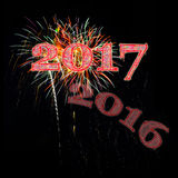 Fireworks celebrating hello 2017 goodbye 2016. Fireworks celebrating 2017 with 2016 fading away evening night sky black background for New Years Day or New Years Royalty Free Stock Photography
