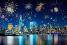 Fireworks celebrating New Years Eve in New York City, NY, USA. With city skyline above the river Royalty Free Stock Photo