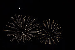 Fireworks couple under a bright full moon. Pair of large gold and white fireworks beneath a bright full moon in a dark rural sky.  3163px X 2109px 300 dpi Stock Photography