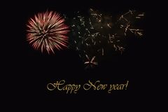 Fireworks on a dark background and a text `Happy New year`. Balanced image for wallpaper, perfect for using as a congratulation card Royalty Free Stock Image