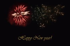 Fireworks on a dark background and a text `Happy New year`. Balanced image for wallpaper, perfect for using as a congratulation card Royalty Free Stock Photos