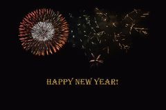 Fireworks on a dark background and a text `Happy New year`. Royalty Free Stock Images