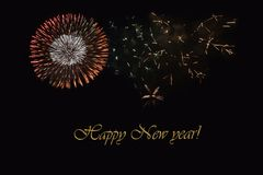 Fireworks on a dark background and a text `Happy New year`. Balanced image for wallpaper, perfect for using as a congratulation card Stock Photo