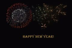 Fireworks on a dark background and a text `Happy New year`. Stock Images