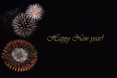 Fireworks on a dark background and a text `Happy New year`. Balanced image for wallpaper, perfect for using as a congratulation card Stock Image