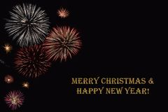 Fireworks on a dark background and a text `Merry Christmas & Happy New year`. Fireworks on a dark background and a text `Merry Christmas & Happy New year` Royalty Free Stock Photography