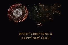 Fireworks on a dark background and a text `Merry Christmas & Happy New year`. Fireworks on a dark background and a text `Merry Christmas & Happy New year` Stock Image